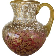 """Moser Signed Cranberry Glass with Gilt Pitcher circa.1880, It's Clear at top down to Cranberry at the bottom - Ornate w/Raised Enamel Vines/Flowers & Leaves decorating the entire body of the Pitcher & heavily gilded, the rim & handle are enamelled in Gold -  Pitcher is signed on the lower body rather than the base 