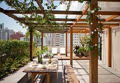 No terraço de 130 m² deste apartamento, há um pergolado e uma mesa grande, na qual o morador serve almoços e jantares para os amigos. Projeto da SAO Arquitetura