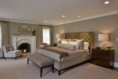 Neutral tones fill this transitional master bedroom, transforming the space into a retreat that feels calm and tranquil. Two armchairs are nestled by the fireplace, providing a spot for fireside conversation or relaxation. | Pulte Homes
