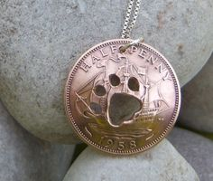 A paw cut into a 1958 halfpenny coin and finished with a sterling silver chain to make a pendant
