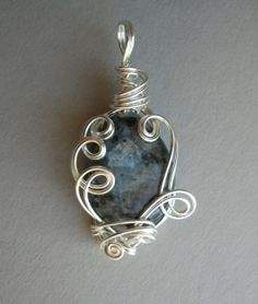 This sculpted wire pendant features a teardrop of larkivite, sometimes called black labradorite.