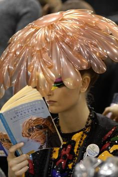 A model reads backstage at John Galliano for Christian DiorHaute Couture Spring/Summer 2008.