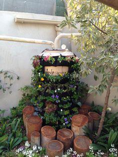 Jojo tank for harvesting rainwater, hidden by wrapping plants around it