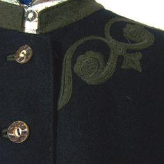 Wunderschöner Mantel aus leichtem, schwarzem Loden, hübsch verziert mit grünen Applikationen und Stickereien, der Stehkragen und die beiden Eingrifftaschen sind mit grünem Loden abgesetzt. Er ist...