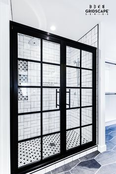 Beautiful black and white master bathroom with double swing French style Gridscape shower doors.