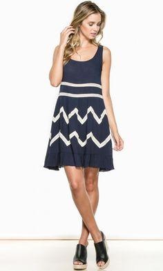 An adorable, sleeveless breezy navy dress with crochet insets and ruffled hem. Fun little summertime dress.