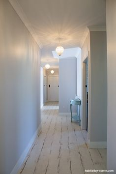 The hallway is painted in Resene Concrete and Resene Black White (trims). It's hard not to admire the beautiful bespoke lighting. http://www.habitatbyresene.co.nz/amy-and-brendon-beach-town-beauty