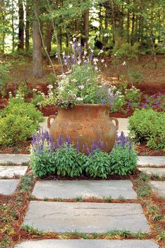 """To accentuate the French Country character of the house, landscape architects Jeffrey Carbo and Kevin Neal placed a parterre garden for herbs, vegetables, and flowers in front. Kevin says, """"Farther away from the house, the plantings are more naturalistic, blending with the wooded surroundings."""" Evergreens provide screening at the sides of the property. Landscape contractor Billy Warren softened the stacked stone front wall with lantana, 'Victoria Blue' salvia, and other perennials. """"Nature…"""