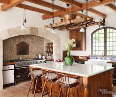 Old-world kitchens often situate the range in a place of honor. In this sizable space, the range is placed in an arched alcove to set it apart from the rest of the room. With countertops on either side, nearbyshelves brimming with spices and seasonings, and a delightfully textured tile backsplash, it's clearthat in this kitchen, the range is its beating heart.