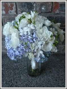 Light blue and lavender hydrangea with stephanotis, white lisianthus and white freesia.  Wrapped with ivory satin ribbon.