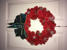 """Pine cone wreath, 12"""" form, all painted cones, hand wired, canvas backing with sparkly snowflake accents."""