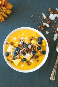 The perfect healthy breakfast with a tropical vibe. Gluten-free, paleo and vegan. - A sweet and tropical mango smoothie bowl is topped with vibrant blueberries, coconut flakes and homemade, gluten-free granola.