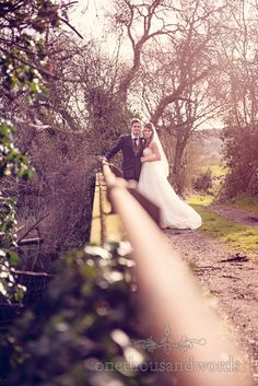 Couple on bridge from wedding at Sopley Mill. Photography by one thousand words wedding photographers