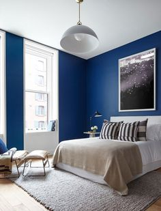 Sanders and Quattrone saw the guest bedroom as an opportunity to go bold with color, choosing Benjamin Moore's Evening Blue for the walls. A sleek bed from the designers' own shop is the perfect match for the industrial pendant by Allied Maker. An accent chair by Environment sits nearby; the artwork is another Consort piece.