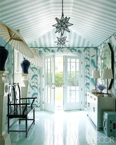 The antique bench and console in this entrance are Chinese. The ceiling fixtures are by Circa Lighting, and the Venetian mirror is fromJohn Rosselli Antiques. The ceiling is papered with a custom-made stripe, the wallpaper is by Lee Jofa, and the floors are painted in a high-gloss custom color by Fine Paints of Europe.