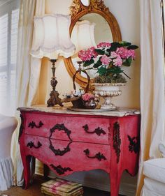 This room has great french elements: A pink bombe chest, an ornate mirror, a beautiful lamp and a mini footstool.