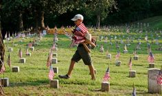 Boy Scout Andrew Conquest of Brandon, Miss., looks for grave markers without a flag, at the Vicksburg National Cemetery Friday, May 25, 2012. Conquest and members of his Brandon, Miss., troop joined with other volunteers to place over 18,000 small American flags on the graves of the Union soldiers and other military  in the cemetery. The flags are placed on the graves only once a year, during the Memorial Day weekend. Photo: Rogelio V. Solis / AP