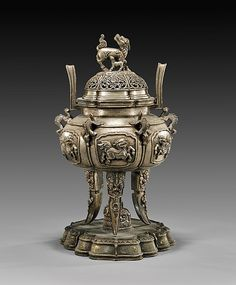 """Elaborately cast, Chinese silvered bronze tripod censer; of somewhat archaistic, lobed form; each panel with prancing qilin reserve, with three lion headed, pointed legs; the reticulated cover with qilin and pup finial; all upon a foliate bronze stand; H: 12"""""""