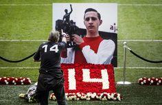 Een man steekt zijn duim op richting de foto van Johan Cruijff. foto: ANP 1 / 6