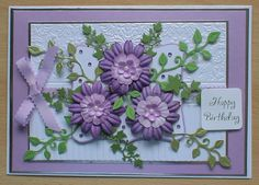 #crafters companion #create and craft  A lilac / purple floral card, I have made this using various dies for the foliage and flowers and a darice embossing folder for the white background, a lilac pearl paper for the background,lilac scallop edged ribbon for the bow and self adhesive gems.