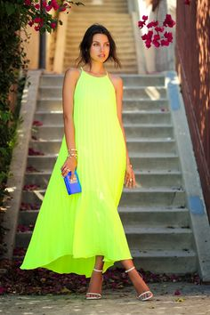 Annabelle Fleur is wearing a neon pleated maxi dress from Line & Dot, clutch from Thale Blanc and the shoes are from Saint Laurent