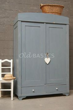 Linnenkast 10021 - Oude linnenkast in een blauwgrijze kleur. De kast staat op sierlijk golvende pootjes en heeft porselein knopjes op de lades. De demontabele kast heeft een hang- en leggedeelte.