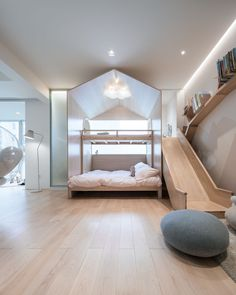 In this modern children's bedroom area, there's a bed built into the play structure with a slide, and on the wall next to the slide is a branch-like wood bookshelf. #KidsBedroom #KidsPlaySpace