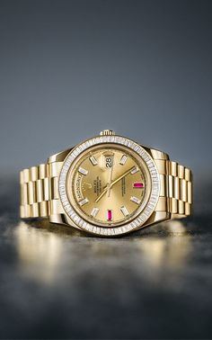 The Rolex Day-Date 40 mm in 18ct yellow gold, with a diamond-set bezel and a champagne dial with hour markers made of baguette-cut diamonds and rubies.