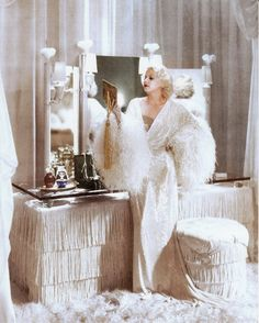 Jean Harlow, born Harlean Harlow Carpenter; (1911-1937) American film actress & sex symbol of the 1930.  Here she is sitting at her 1930s fringed Art Deco dressing table