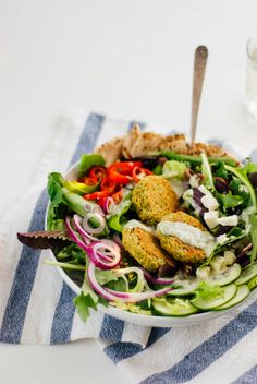 This fresh green salad features crispy baked falafel for protein! Plus delicious Mediterranean toppings: cucumber, olives, cherry tomatoes, onion, pita wedges and tahini sauce. #falafelsalad