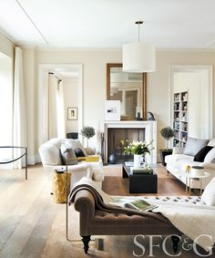 Elegant living room with neutral palette, pendant light, topiaries and dual white sofas #SFC&G
