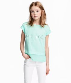Short-sleeved top in soft cotton jersey with a printed motif at front and slits at sides. Shorter at front with extended, sheer hem.