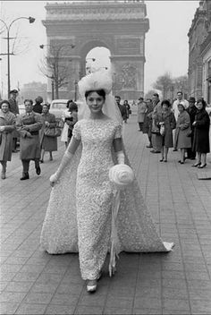 Model wearing a wedding dress on the Champs Elysees, Paris, 1961. Photo by Frank Horvat.  The Swinging Sixties