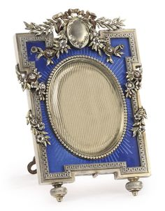 A FABERGÉ SILVER AND TRANSLUCENT ENAMEL PHOTOGRAPH FRAME, MOSCOW, CIRCA 1895. shaped rectangular, enamelled translucent blue over a sunburst guilloché ground, applied with foliate swags and ribbons, beaded bezel surrounding oval aperture, with wood back and shaped silver strut, struck K. Fabergé with Imperial Warrant, 88 standard, scratched inventory number 5536. Diameter 4 3/8 in.; 11 cm
