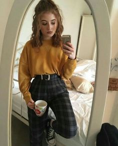 Yellow jumper and patterned trousers with a belt.