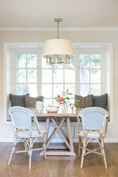Breakfast room boasts a built-in window seat nook lined with gray cushions and pillows facing a ...