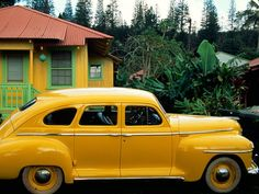 The yellow hues of a small home in Lanai City, Hawaii, are matched by its owner's vintage Plymouth. Many residents of this village live in such pastel-painted cottages, first built for pineapple plantation workers. Photograph by Jim Richardson