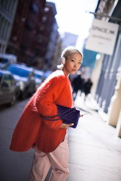 Vanessa Hong of The Haute Pursuit embraces colors in a red, oversized shaggy cardigan + baggy pale pink trousers + purple clutch