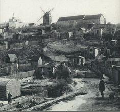 """Une vue de la butte Montmartre et du """"maquis"""" vers 1890. Les rues ne sont que des chemins et les maisons pas plus que des cabanes. En fait, c'était la misère, rien de bien pittoresque... En haut, les ailes du Moulin de la Galette (photo anonyme)."""