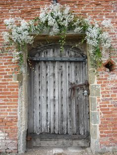 Entrance to The Walled Garden decorated with clouds of gypsophila and ivy by Spriggs Florist