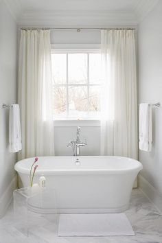 bathroom window White sheer curtains dress a window placed above a freestanding oval bathtub paired with a polished nickel floor-mount tub filler alongside a small lucite waterfall accent table situated on a white marble herringbone pattern tiled floor. Bathroom Window Treatments, Bathroom Windows, Bathroom Floor Tiles, Bathroom Curtains, Shower Curtains, Tile Floor, Tub Tile, Shower Floor, Small Window Curtains
