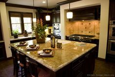 A gourmet #kitchen with dark wood cabinets and an island with seating. Gourmet Kitchen Design #01 (Kitchen-Design-Ideas.org)