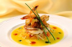 Grilled shrimp on sea bass atop mandarin orange slaw and mango sauce with chili sauces.