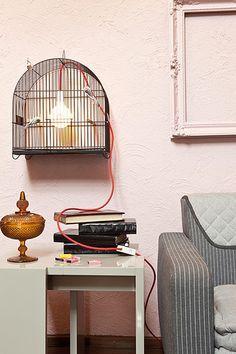 Para iluminar este ambiente de forma inusitada, o pendente Nud Classic foi colocado dentro da gaiola e combinado com passarinhos decorativos pintados de prata. Ideia criativa do designer Marcus Ferreira