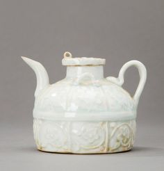 A small Qingbai ewer and cover, Yuan Dynasty, 1280-1368 with two shoulder lugs, the body divided into two sections, each one with eight moulded panels of flowers, unglazed base 8cm high