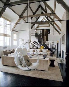 Indoor Swing, via WooHome | lucite indoor swing | living room design | exposed beams | suspended chair | black and beige decor | contemporary interior design |