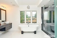 """The spacious master en suite has clean lines and a black-and-white colour scheme. Black blocks act as feet on this stand-alone bathtub.   See more of this home in """"Bright Home on Secret Ottawa Lake Goes Modern"""" from OUR HOMES Ottawa Summer 2016 http://www.ourhomes.ca/articles/build/article/bright-home-on-secret-ottawa-lake-goes-modern"""