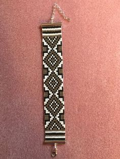 This beautiful bracelet was made on my loom with size 11 Japanese seed bead of white, silver and black. it was woven with white Nymo thread and finished with a