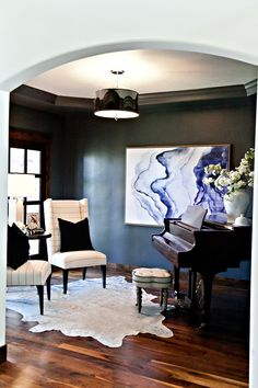 Formal sitting room with metallic cowhide rug, navy walls, grand piano and abstract indigo ink artwork