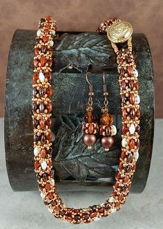 This is the season to let your hair down and don your finest. This beaded rope and earring set will definitely demand attention.  The beads are czech glass SuperDuos in shades of brown, bronze, chocolate, and white pearl and high quality Japanese Toho glass seed beads in shimmering metallic antique gold. The earrings are a repeat of the necklace design and embellished with amber faceted fire polished crystals. Ive photographed this set with different textures to give an idea of how it will…
